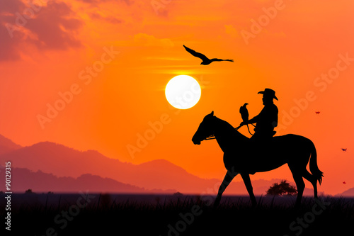 Poster Corail silhouette of Cowboy sitting on his horse at sunset background