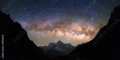 Photo Stands Night Bowl of Heavens. Bright and vivid Milky Way galaxy over the snowy mountains. Beautiful starry night sky seems to be in a