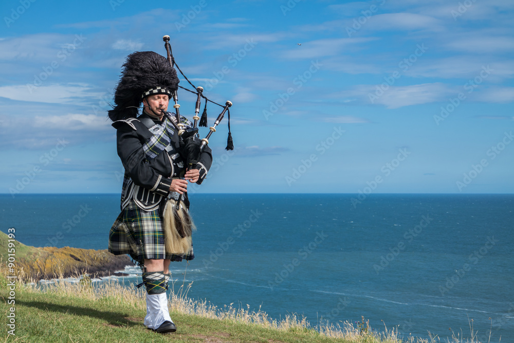 Fototapeta Traditional scottish bagpiper in full dress code with the sea in background