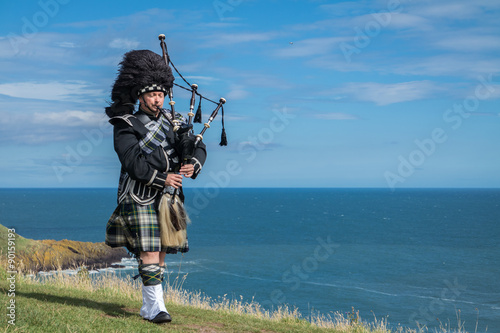 Fotografering Traditional scottish bagpiper in full dress code with the sea in background