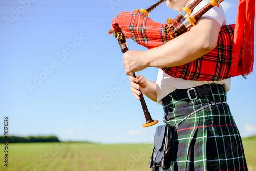 Fotografie, Obraz Muž hraje skotské tradiční trubky na zelené létě venku