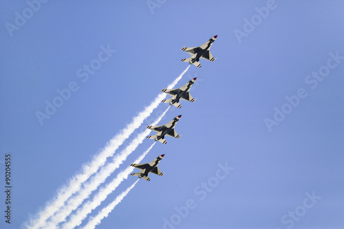Fotografia, Obraz Four US Air Force F-16C Fighting Falcons, known as the Thunderbirds, flying in formation with white trailer of smoke over the 42nd Naval Base Ventura County (NBVC) Air Show at Point Mugu, Ventura County, Southern California