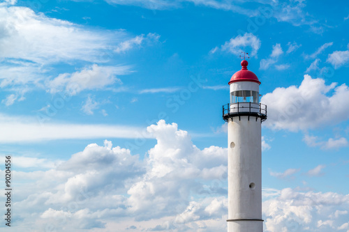Foto op Aluminium Vuurtoren Brick white lighthouse with red top against blue sky with clouds in Hellevoetsluis, the Netherlands