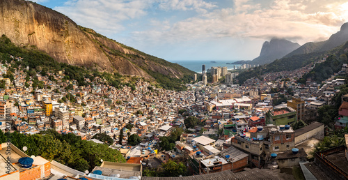 Panoramic view of Rio's Rocinha favela, on a sunny afternoon.  Visible in the distance is the South Atlantic Ocean. The high-rise buildings near the coast are condominiums in Sao Conrado