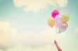 canvas print picture - Girl hand holding multicolored balloons done with a retro vintage instagram filter effect, concept of happy birth day in summer and wedding honeymoon party (Vintage color tone)