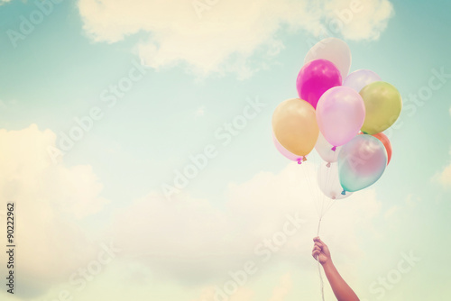 Fotografie, Tablou  Girl hand holding multicolored balloons done with a retro vintage instagram filt