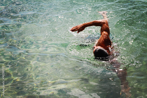 Fotografia, Obraz  Strong muscular man swimming in the sea ocean scrawl style