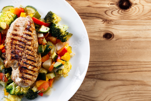 obraz dibond Grilled chicken fillet, breast with cooked vegetable Tomatoes, Carrots, Peppers, Courgettes, brocoli on plates.