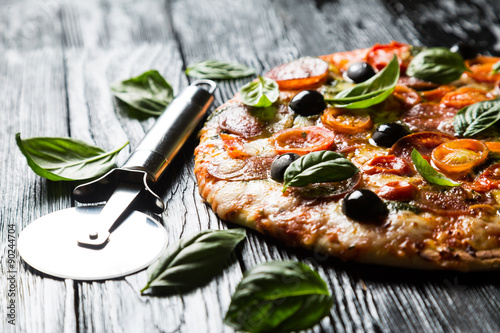 Photo  Pizza with salami, olives and basil