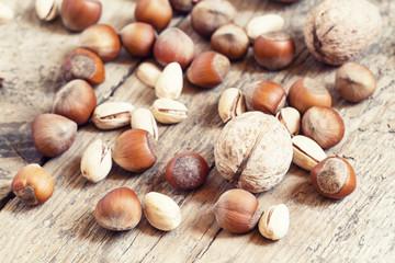 Fototapeta Walnuts, hazelnuts and pistachios on a wooden table