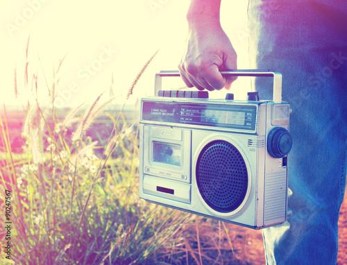 Poster Retro Man hand holding vintage radio on nature background