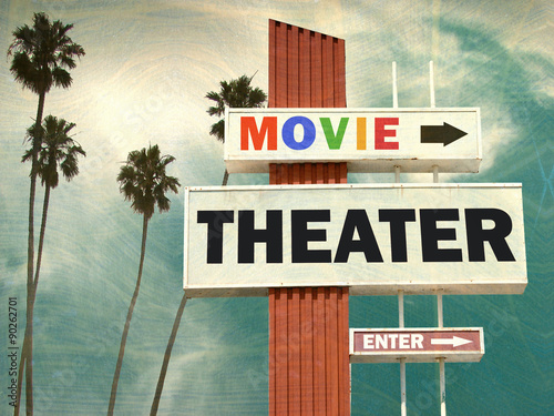 Photo  aged and worn vintage photo of movie theater sign with palm trees