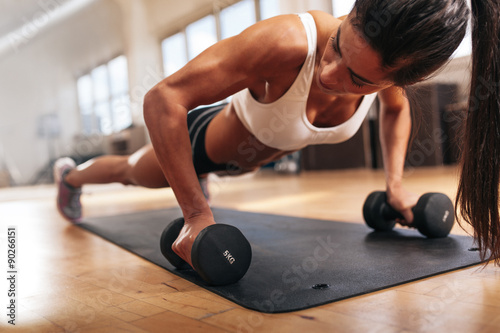 Poster  Gym woman doing pushups on dumbbells