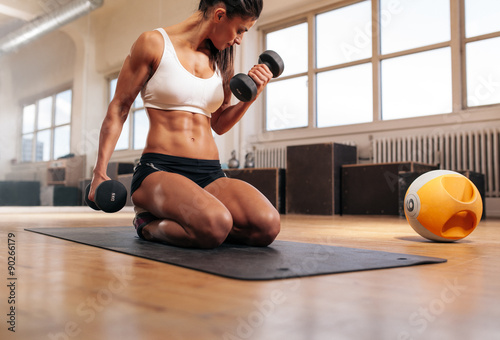 Tela  Fit woman working out at the gym with dumbbells