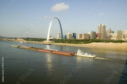 Fotografia  Daytime view of tug boat pushing barge down Mississippi  River in front of Gateway Arch and skyline of St