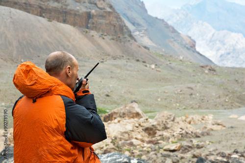 Man Talking on Radio Mountain Rescue Officer Holding Radio Walkie Talkie and Sev Fototapeta