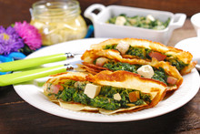 Spinach And Feta Filled Pancakes On Wooden Table