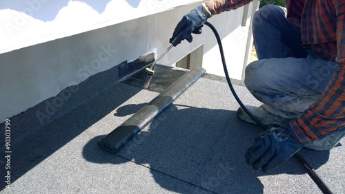 Roofer preparing part of bitumen roofing felt roll for melting by gas heater tor Canvas Print