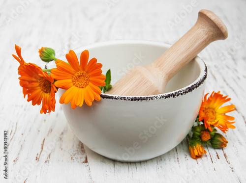Obraz flower of calendula officinalis in mortar - fototapety do salonu