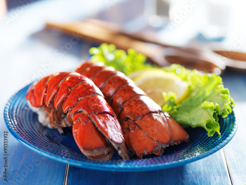 фотографія  two lobster tails on blue plate with garnish for dinner