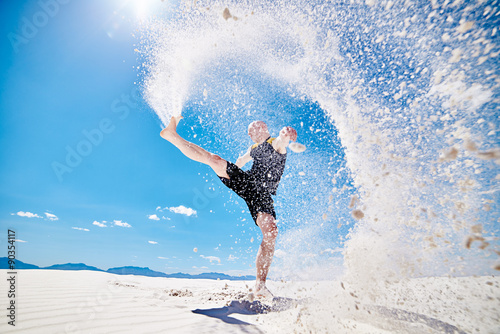 action photo of man kicking huge trail of sand into the air while doing martial arts
