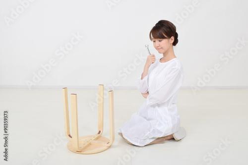 Fotografie, Obraz  スパナで椅子を組み立てる女性