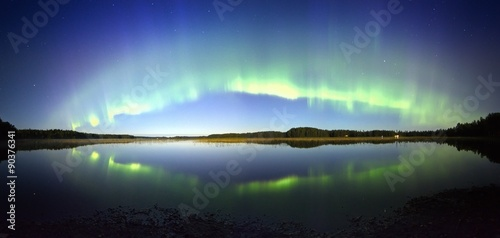 Foto auf Gartenposter Nordlicht Northern lights panorama with reflection on the lake at night.