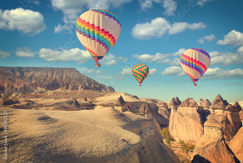 Vintage photo of hot air balloon flying over rock landscape at Cappadocia Turkey.