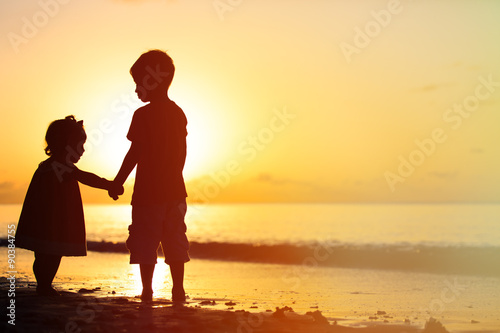 little boy and girl holding hands at sunset Canvas Print