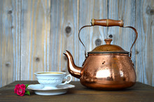 Old Copper Teapot And Porcelain Teacup On Wooden Table