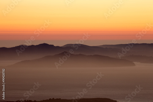 Fototapeta Hazy sunset over Angel Island and the Marin Hills of the Golden-Gate National Recreation Area