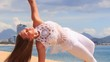 blonde girl in lace shows yoga asana half moon on beach
