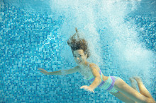 Girl Jumps And Swims In Pool Underwater, Happy Active Child Has Fun In Water