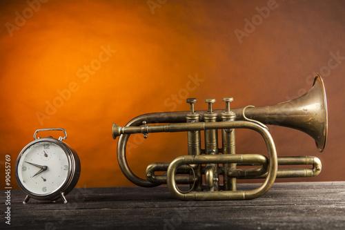 fototapeta na ścianę Tromba in ottone con sveglia su piano di legno e sfondo arancio
