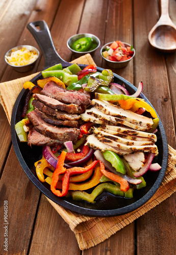 Photo  chicken and steak mexican fajitas in iron skillet