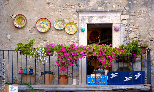 Peschici, apulia. old town balcony with small shop, artistic picture
