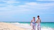 Young couple holding hands running on tropical sandy beach in white dresses