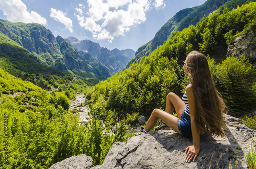 Photo Young woman sitting on a rock and looking at beautiful mountains