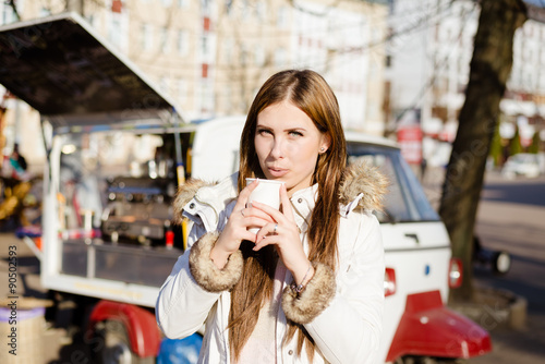 Spoed Foto op Canvas Chocolade Girl wearing coat holding cup with drink near street food.