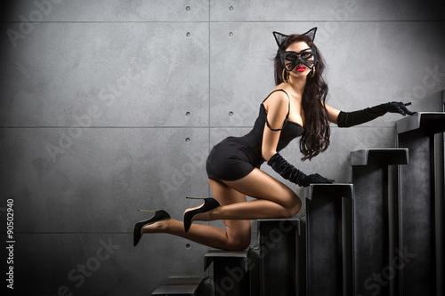 Fotografie, Obraz Sexy žena v obleku Catwoman ležící na schodech