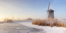 Dutch Windmills In A Foggy Winter Landscape In The Morning