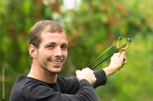 Valokuvatapetti Handsome man concentrated aiming  a slingshot at park having fun