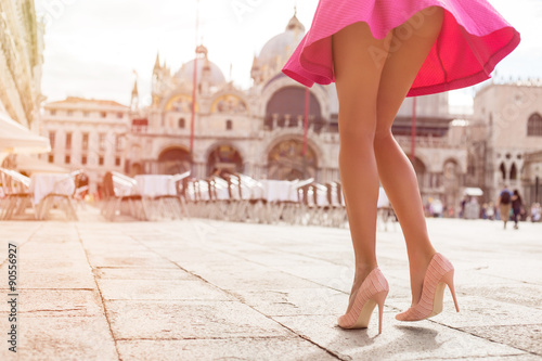 Fotografia Fashionable woman with pink skirt and high heel shoes on St Marks Square in Veni