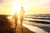 Fototapeta Fototapety z morzem do Twojej sypialni - Zabawa przy zachodzie słońca. Dzieci  bawią się na brzegu morza podczas zachodu słońca