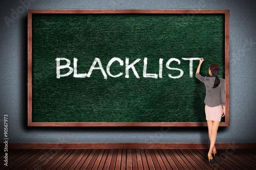Businesswoman drawing blacklist  on chalkboard Canvas Print