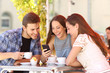 canvas print picture - Friends watching media in a smart phone in a coffee shop