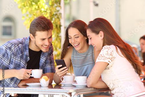 Zdjęcie XXL Przyjaciele ogląda środki w mądrze telefonie w sklep z kawą