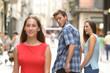 Leinwandbild Motiv Disloyal man with his girlfriend looking at another girl