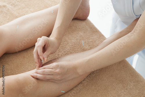 Photo Acupuncturist, pointing to acupuncture to women's knee