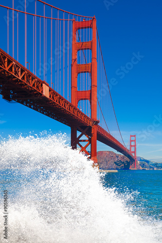 Photo  Golden Gate Bridge with big wave splash and spray in the foregro
